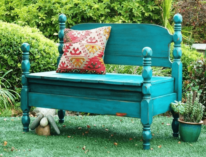 up-cycled headboard bench painted in teal and set in outdoor setting