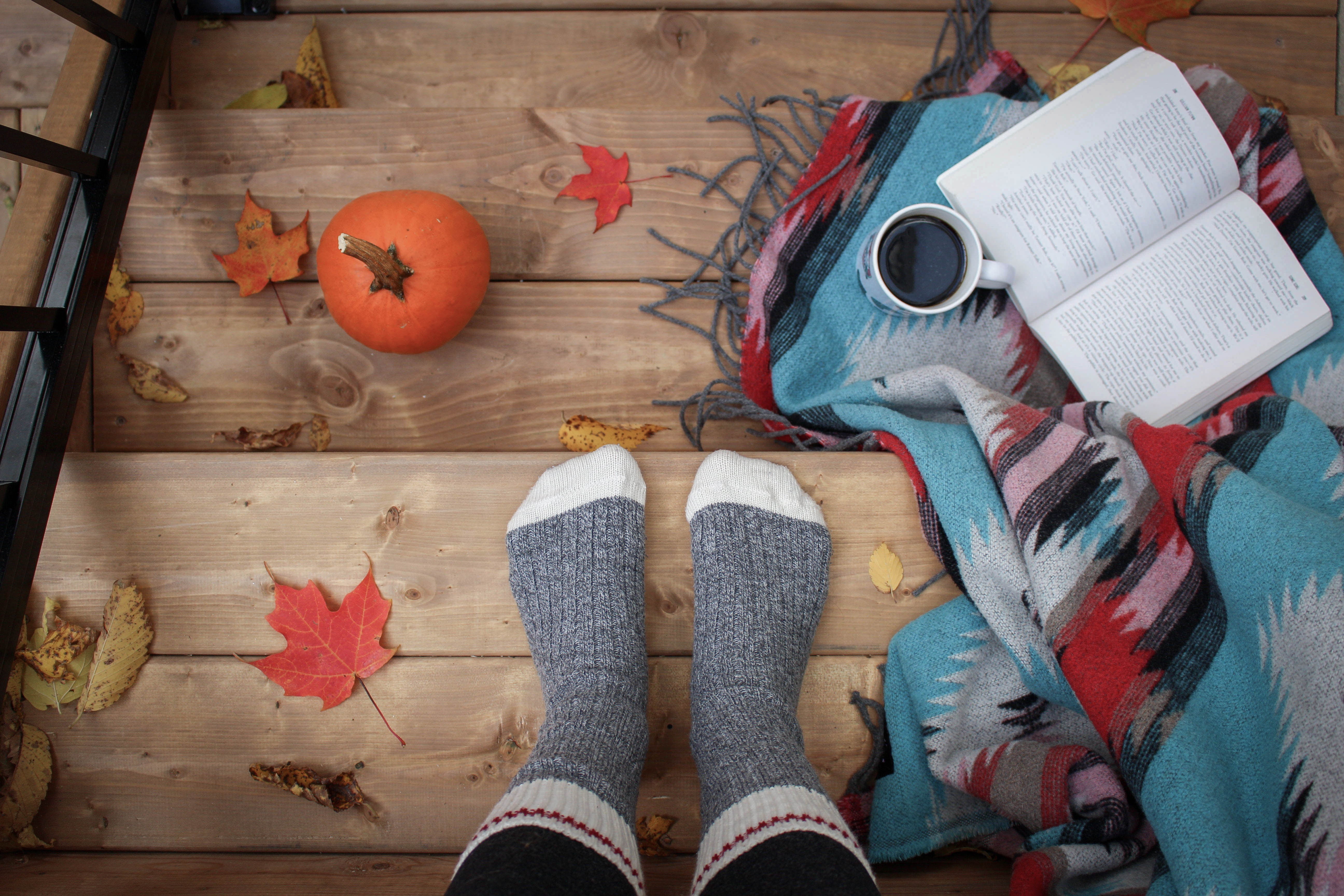 porch steps with view of feet with socks and fall foliage with a pumpkin, coffee and book
