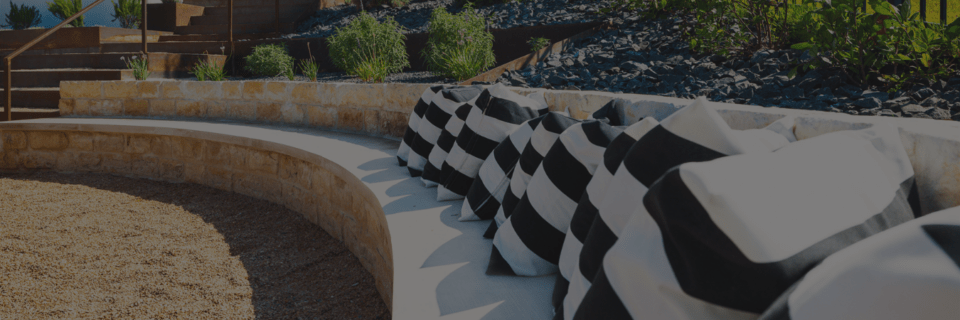 Built-in outdoor seating of natural stone with striped pillows and next to tiered landscape design with rock and plant installation