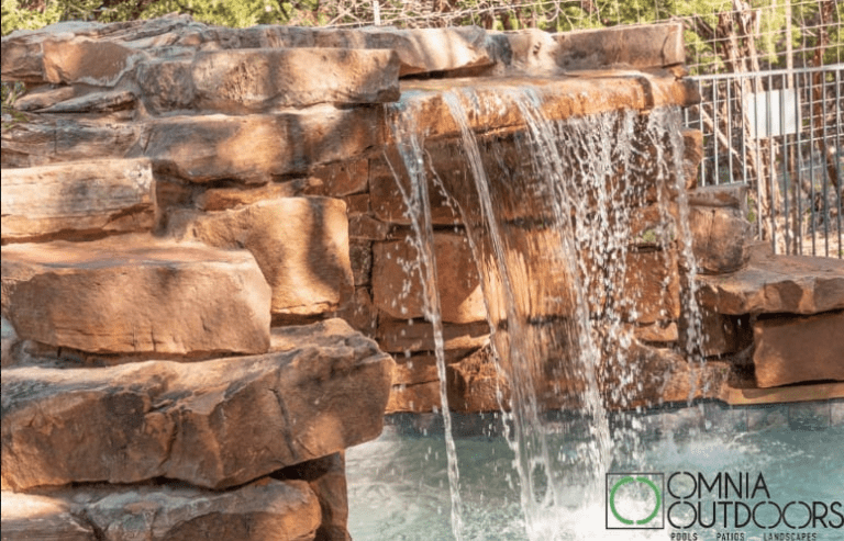 pool with waterfall water feature by Omnia Outdoors, partnered with Best of Texas Landscapes